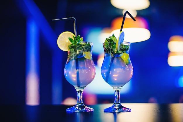 Dois copo de mojito cocktail com palhas de limão e hortelã na festa Foto Premium