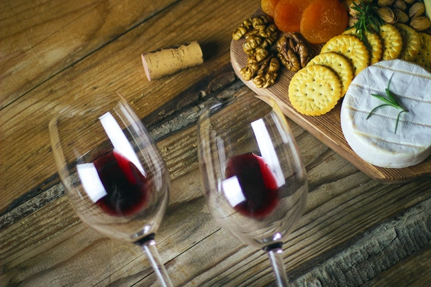 Dois copo de vinho tinto e queijo prato vista superior Foto gratuita