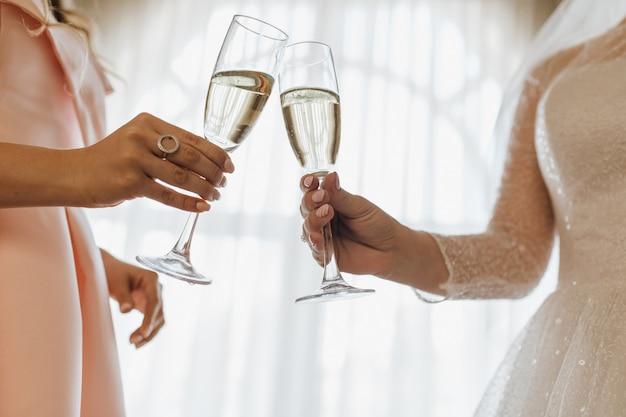 Dois copos cheios de champanhe nas mãos da noiva e dama de honra Foto gratuita