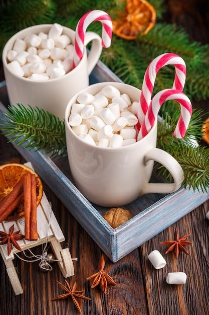 Dois copos com pequenos marshmallows em um fundo escuro de madeira Foto Premium