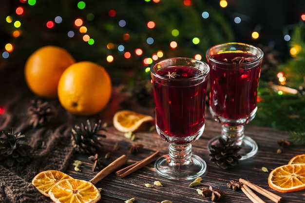 Dois copos com vinho quente na mesa com fatias de laranja e especiarias Foto Premium