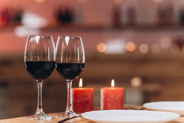 Dois copos com vinho tinto e velas acesas em um close-up de mesa servida Foto Premium