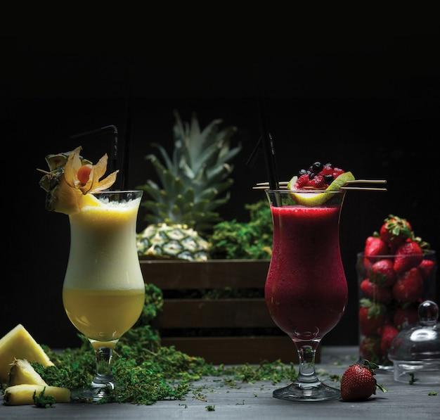 Dois copos de abacaxi e smoothies de morango Foto gratuita