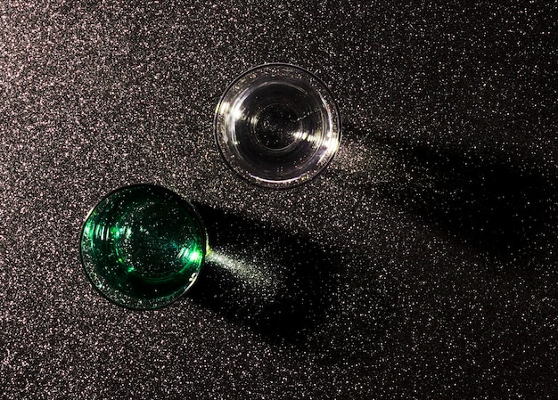 Dois copos de água no fundo preto brilhante Foto gratuita