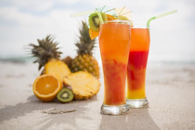 Dois copos de bebida cocktail e frutas tropicais mantidos na areia Foto gratuita