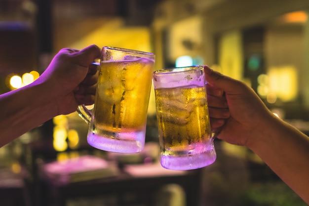Dois copos de cerveja vibra juntos entre amigo no bar de baixa luz e restaurante Foto Premium
