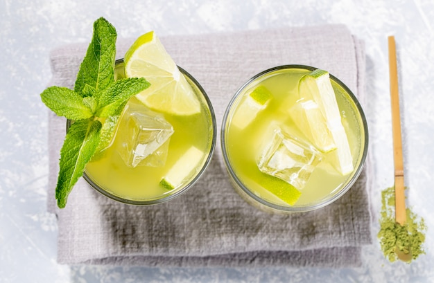 Dois copos de chá matcha verde gelado com limão, gelo, hortelã e colher de pau de pó em cinza. vista do topo. Foto Premium