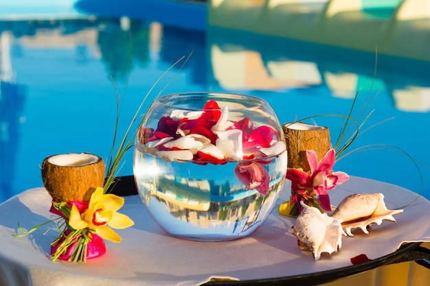 Dois copos de coco com orquídeas, duas conchas e pétalas de rosa em um aquário Foto Premium