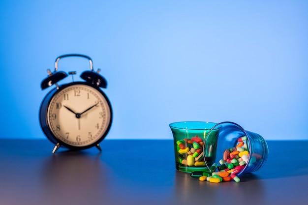 Dois copos de medição com remédios espalhados ao lado de um despertador preto vintage. o conceito do tempo que passa. Foto Premium