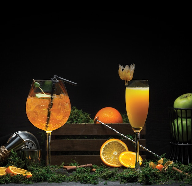 Dois copos de suco de laranja com e sem cubos de gelo. Foto gratuita