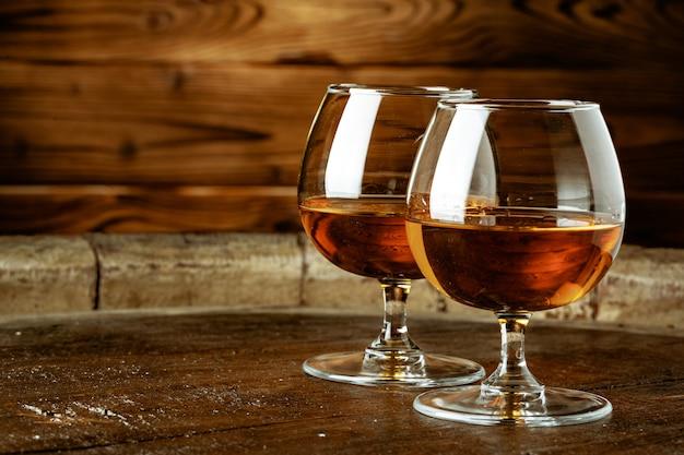 Dois copos de uísque em uma mesa de madeira no bar Foto Premium