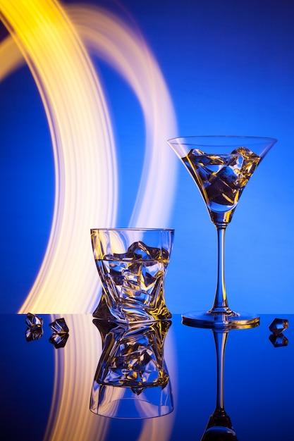 Dois copos de um cocktail martini whisky gelo, contra o azul de belos efeitos de luz. Foto Premium