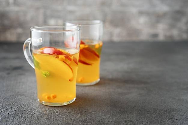 Dois copos de vidro com chá de maçã na superfície cinza Foto Premium