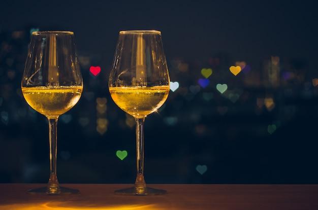Dois copos de vinho branco na mesa de madeira do bar no terraço Foto Premium