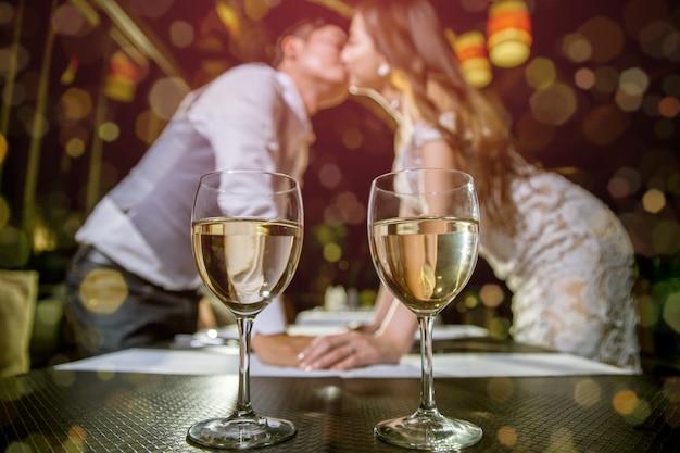 Dois copos de vinho lugar na mesa. há pares asiáticos que beijam junto no fundo blured. Foto Premium