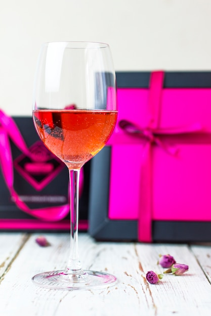 Dois copos de vinho rosé na mesa de madeira branca com caixas de presente rosa Foto gratuita