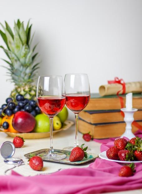 Dois copos de vinho rosé na mesa de madeira branca com livros antigos e relógio, diferentes frutas tropicais e morangos Foto gratuita