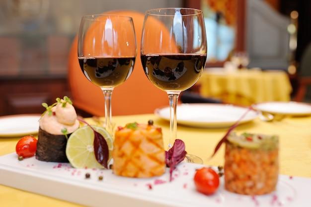 Dois copos de vinho tinto no fundo das delícias no restaurante Foto Premium