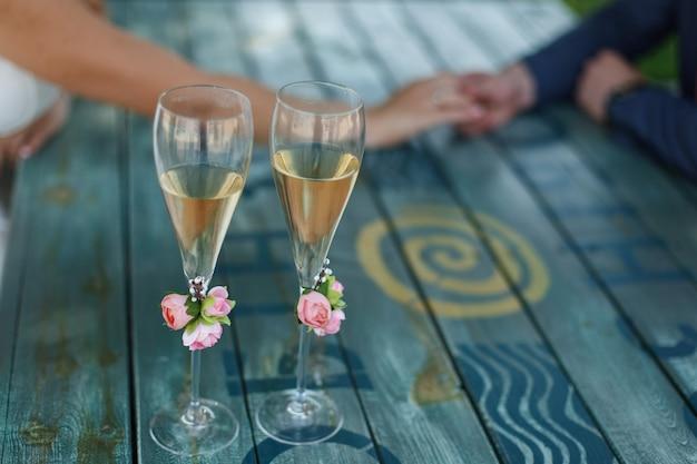 Dois copos decorados com champanhe em cima da mesa no dia do casamento. local de comemoração. Foto Premium