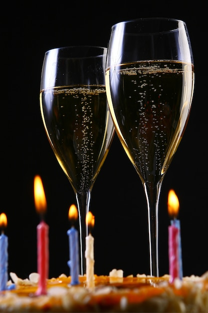 Dois copos elegantes com champanhe e bolo de ouro Foto gratuita