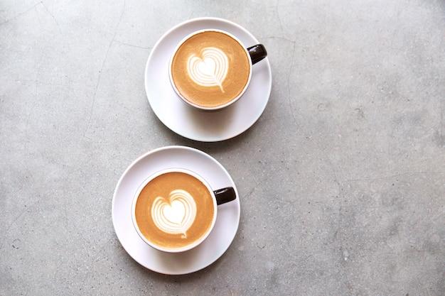 Dois copos pretos do cappucino saboroso com latte da arte do amor. Foto Premium
