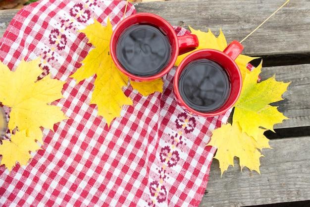 Dois copos vermelhos em lençóis amarelos, outono Foto Premium
