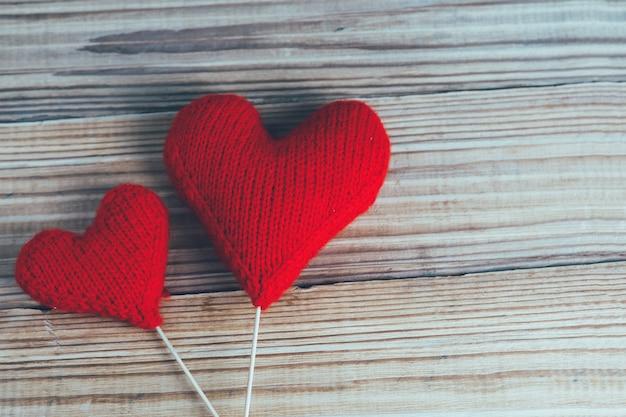 Dois corações feitos malha vermelhos no fundo de madeira. o conceito de dia dos namorados Foto Premium