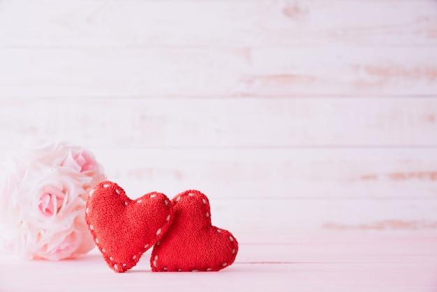 Dois corações vermelhos com flor rosa rosa sobre fundo de madeira. Foto Premium