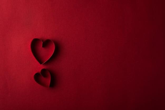 Dois corações vermelhos contra o fundo vermelho Foto gratuita