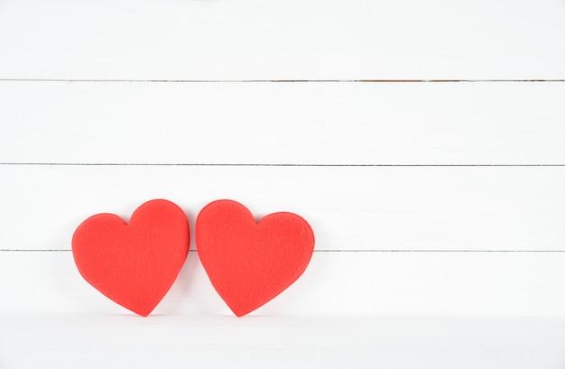 Dois corações vermelhos em fundo branco de madeira. conceito de amor. dia dos namorados. conceito de saúde. Foto Premium