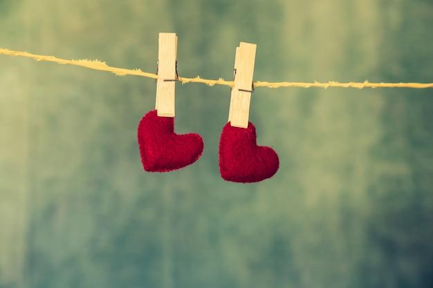 Dois corações vermelhos estão pendurados na corda sobre o fundo azul de madeira. Foto gratuita