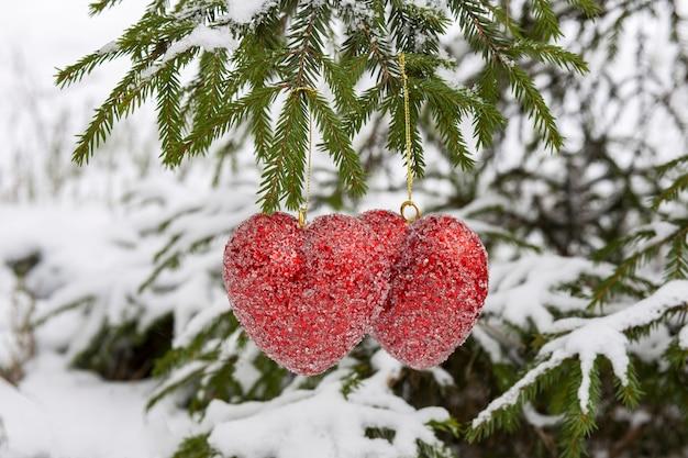 Dois corações vermelhos penduram em uma árvore. plano de fundo: natal, dia dos namorados, ano novo, casamento Foto Premium