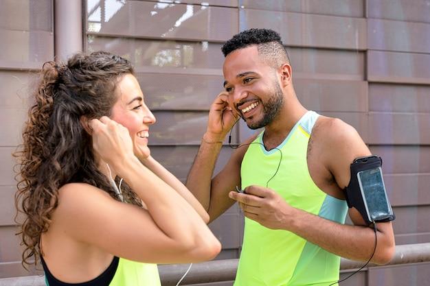 Dois corredores sorrindo alegremente colocando os fones de ouvido nos ouvidos, conectando-os aos smartphones Foto Premium