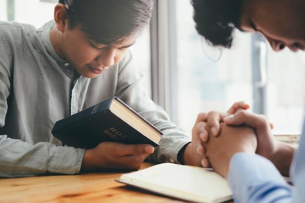 Dois cristãos estão orando juntos pela bíblia sagrada. Foto Premium