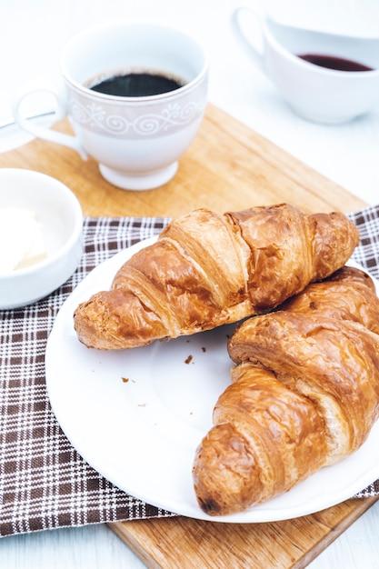 Dois croissants caseiros com café na mesa. chá e doces no café da manhã. Foto Premium