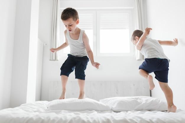 Dois, cute, irmãos, tendo divertimento, cama Foto gratuita