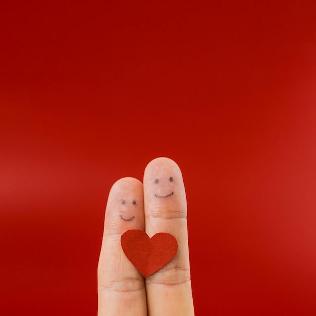 Dois dedos, pintado, com, faces felizes Foto gratuita