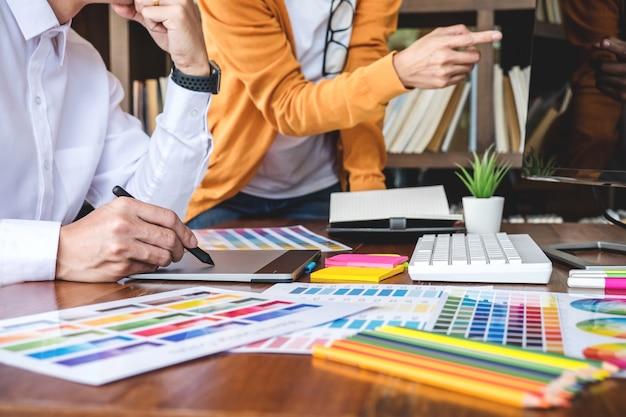 Dois designer gráfico trabalhando na seleção de cores e desenho na mesa digitalizadora Foto Premium