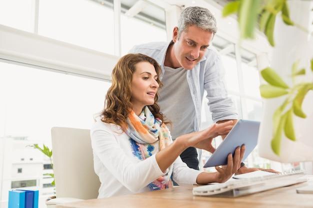 Dois designers casuais trabalhando com tablet no escritório Foto Premium