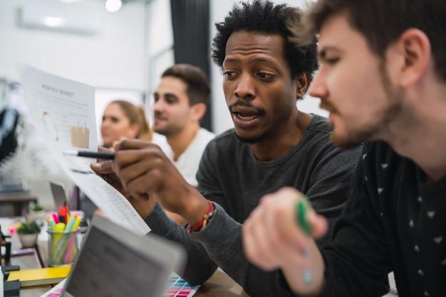 Dois designers criativos trabalhando juntos em um projeto e compartilhando novas ideias no local de trabalho. conceito de trabalho em equipe e negócios. Foto gratuita