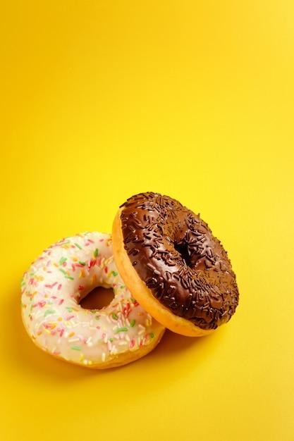 Dois donuts preto e brancos na parede amarela Foto Premium