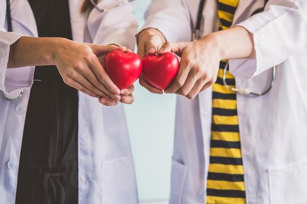 Dois doutores que guardam o coração vermelho, conceito dos cuidados médicos. Foto Premium