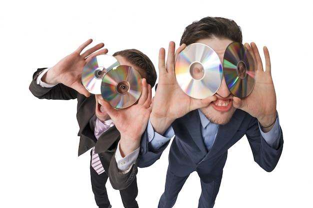 Dois empresários alegres que oferecem dvds à venda Foto gratuita