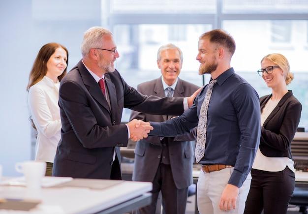 Dois empresários apertando as mãos parabenizando na promoção Foto gratuita