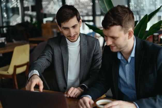 Dois empresários apontando a tela do laptop enquanto discutia Foto gratuita