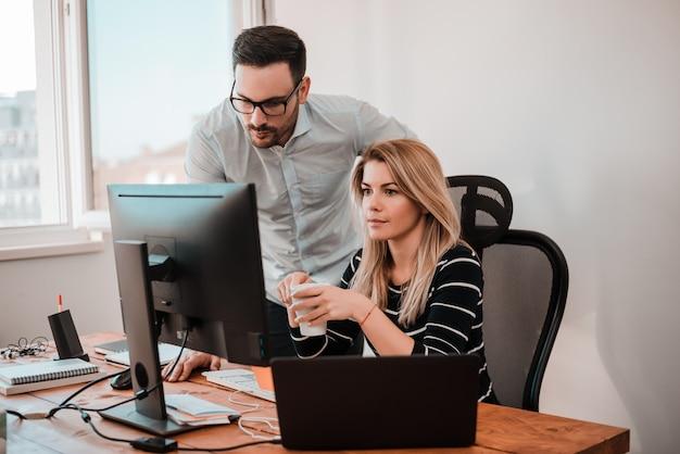 Dois empresários coworking com um computador em uma mesa no escritório. Foto Premium