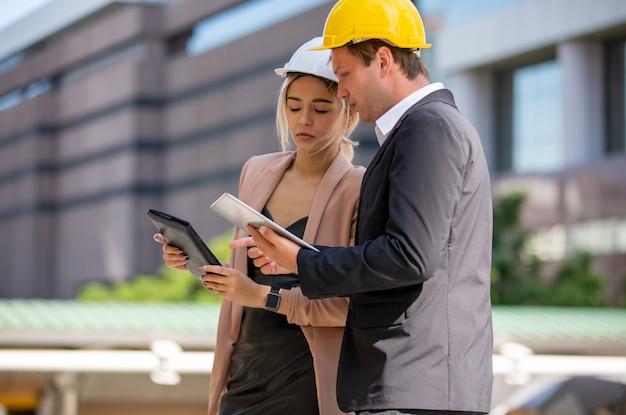 Dois empresários e mulher vestindo coletes de segurança conversando e aperto de mão no canteiro de obras Foto Premium