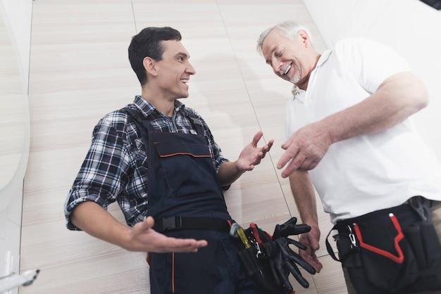 Dois encanadores consertam a torneira do banheiro Foto Premium
