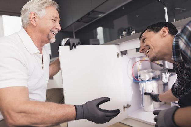 Dois encanadores estão preparados para reparar o filtro de água. Foto Premium