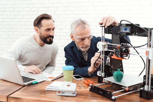 Dois engenheiros imprimem os detalhes na impressora 3d. Foto Premium